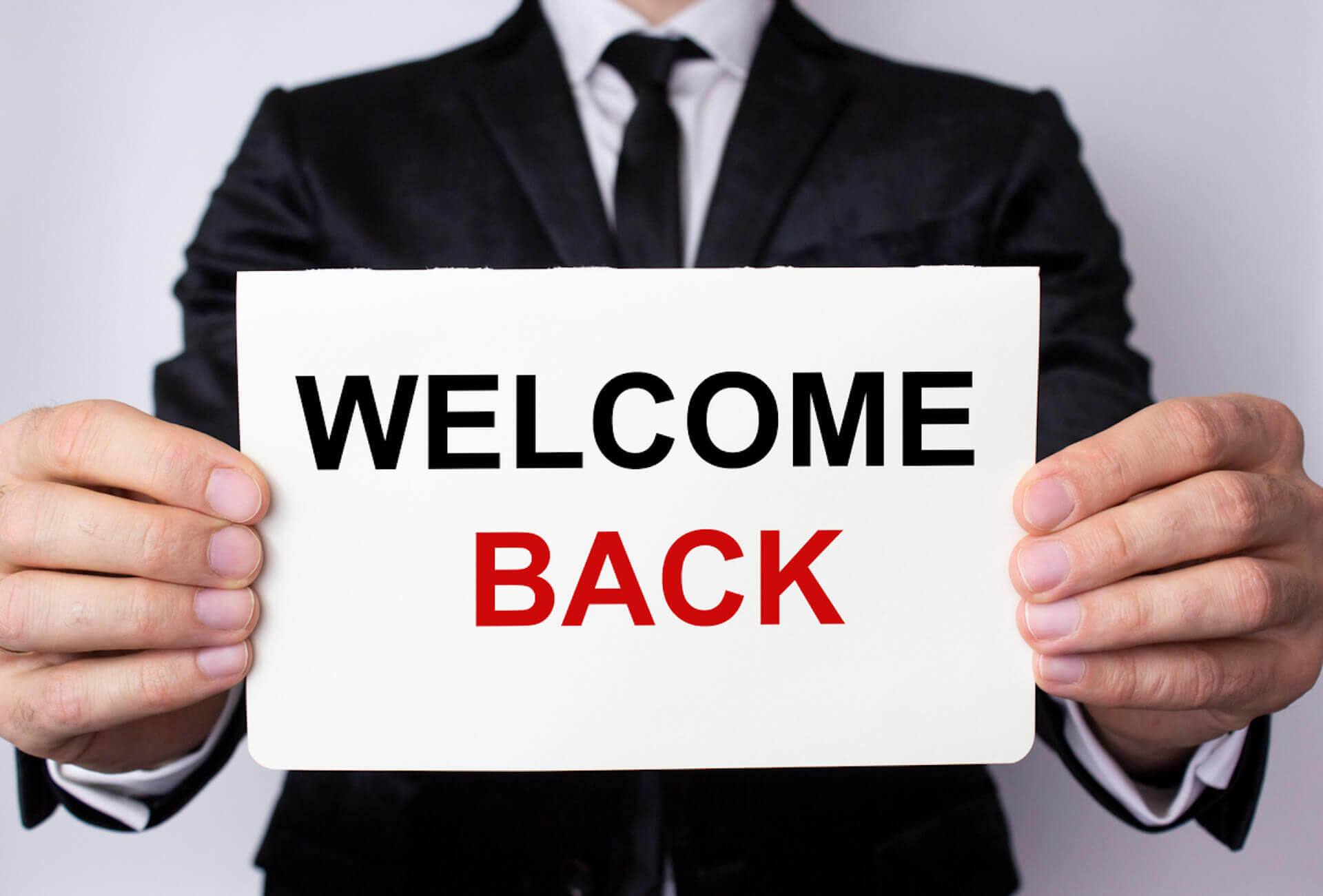 """Man holding """"Welcome Back"""" Sign"""